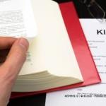 Klage mit Buch, Hand und Brille
